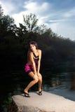Mooie jonge vrouw die zich door de rivier bevinden stock foto