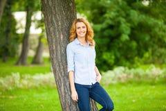 Mooie jonge vrouw die zich naast een boom bevinden stock foto