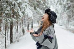 Mooie jonge vrouw die zich onder sneeuwbomen in de winterbos bevinden en van sneeuw genieten stock fotografie