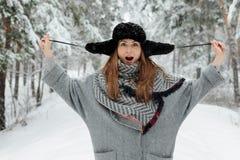 Mooie jonge vrouw die zich onder sneeuwbomen in de winterbos bevinden en van sneeuw genieten royalty-vrije stock foto's
