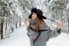 Mooie jonge vrouw die zich onder sneeuwbomen in de winterbos bevinden en van sneeuw genieten royalty-vrije stock fotografie
