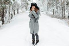 Mooie jonge vrouw die zich onder sneeuwbomen in de winterbos bevinden en van sneeuw genieten stock foto