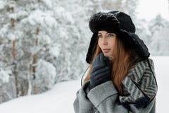 Mooie jonge vrouw die zich onder sneeuwbomen in de winterbos bevinden en van sneeuw genieten royalty-vrije stock afbeeldingen