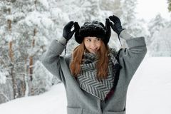 Mooie jonge vrouw die zich onder sneeuwbomen in de winterbos bevinden en van sneeuw genieten stock afbeeldingen