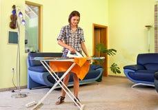 Mooie jonge vrouw die zijn kleren thuis strijkt. Stock Afbeeldingen