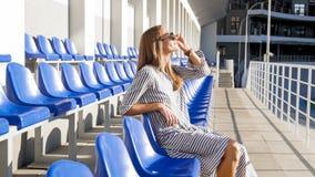 Mooie jonge vrouw die zonnebril dragen die op lege rijen van zetels bij stadion zitten Stock Afbeelding