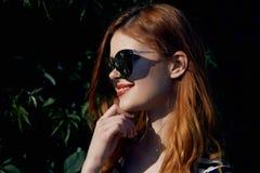 Mooie jonge vrouw die in zonnebril langs de straat lopen Royalty-vrije Stock Foto's