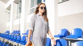 Mooie jonge vrouw die in zonnebril tussen rijen van zetels op stadion lopen Royalty-vrije Stock Afbeeldingen