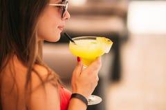 Mooie jonge vrouw die zwempak dragen die een kleurrijke cocktailzitting op een cabine van de bar van de strandclub drinken stunni stock foto