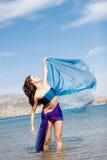 Mooie jonge vrouw door het strand royalty-vrije stock afbeelding