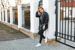 Mooie jonge vrouw in een bommenwerpersjasje met zwarte jeans royalty-vrije stock afbeelding