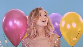 Mooie jonge vrouw in een gouden kleding bij een partij Zij glimlacht en heeft pret op een blauwe achtergrond onder stock video