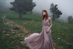 Mooie jonge vrouw in een lange kleding in de bergen, mist Stock Foto's