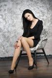 Mooie jonge vrouw in een leunstoel stock afbeelding