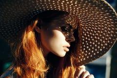 Mooie jonge vrouw in een rieten hoed, portret, zon, de zomer stock afbeelding