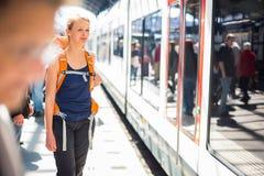 Mooie, jonge vrouw in een trainstation, die op haar trein wachten Stock Afbeeldingen
