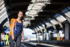 Mooie, jonge vrouw in een trainstation, die op haar trein wachten Stock Foto's