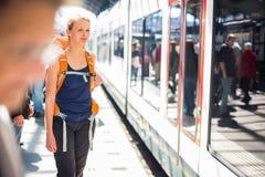 Mooie, jonge vrouw in een trainstation, die op haar trein wachten Royalty-vrije Stock Foto's