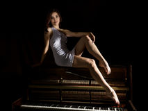 Mooie jonge vrouw in een witte kleding met een open achterzitting op een oude piano op een donkere achtergrond Royalty-vrije Stock Afbeelding