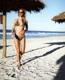 Mooie jonge vrouw in een zwempak op het strand Stock Afbeeldingen