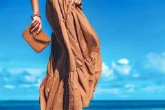 Mooie jonge vrouw in elegante kleding met koppeling op het strand royalty-vrije stock afbeelding