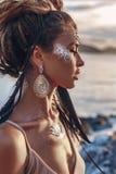 Mooie jonge vrouw in elegante kleding op het strand bij zonsondergang stock foto's