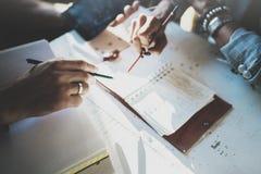 Mooie jonge vrouw en haar partner die iets in notastootkussen schrijven terwijl het zitten op leunstoel bij woonkamer charming royalty-vrije stock foto's