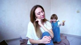 Mooie jonge vrouw en moeder die en in camera op achtergrond van kleine dochter glimlachen stellen die binnen op vloer speelt stock footage