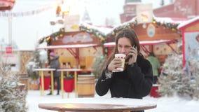 Mooie jonge vrouw gebruikend een smartphone en drinkend hete thee tijdens de Kerstmismarkt stock videobeelden
