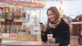 Mooie jonge vrouw gebruikend een smartphone en drinkend hete thee tijdens de Kerstmismarkt voor carrousel stock footage