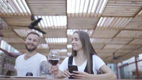 Mooie jonge vrouw gebruikend moderne slimme telefoon in de koffie en typend tekstbericht op cellphone stock footage