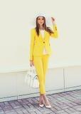 Mooie jonge vrouw in gele kostuumkleren en hoed, handtas Stock Fotografie