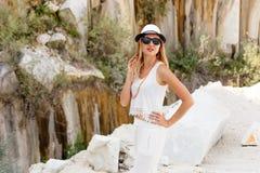 Mooie jonge vrouw in glazen en een hoed op een marmeren steengroeve stock foto