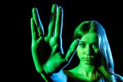 Mooie jonge vrouw in groen licht die het vreemde teken tonen Stock Afbeeldingen