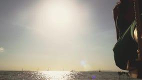 Mooie jonge vrouw in groene kleding die op een schommeling bij zonsondergang op het strand slingeren Langzame Motie 1920x1080 stock footage