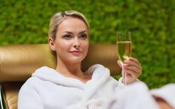 Mooie jonge vrouw het drinken champagne bij kuuroord royalty-vrije stock fotografie