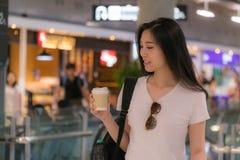 Mooie jonge vrouw het drinken koffie Voor het gedrang en bustleof van het reizen stock foto's