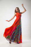 Mooie jonge vrouw in het heldere kleurrijke kleding dansen Royalty-vrije Stock Foto's