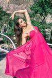 Mooie jonge vrouw in het lange roze avondjurk stellen in aard, die het ontwikkelen stock afbeelding