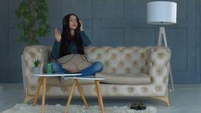 Mooie jonge vrouw het luisteren muziek in hoofdtelefoons stock footage