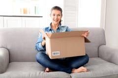 Mooie jonge vrouw het openen doos met pakket stock foto's