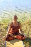 Mooie jonge vrouw het praktizeren yoga op mat in openlucht bij rivierbank op gras Stock Foto's