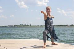 Mooie jonge vrouw het praktizeren yoga in openlucht in ochtend royalty-vrije stock foto