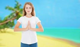 Mooie jonge vrouw het praktizeren yoga in het tropische strand en het maken van namaste mudra royalty-vrije stock foto