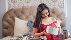 Mooie jonge vrouw in het rode kleding het glimlachen openen giftbox en teleurgesteld van huidig middelgroot schot stock videobeelden