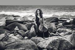 Mooie jonge vrouw het spelen cello op steenstrand bij stormachtige wea stock foto's
