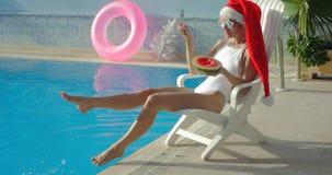 Mooie jonge vrouw in het zwembad van de Kerstmanhoed dichtbij stock video