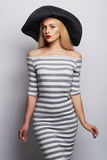 Mooie jonge vrouw in hoed het meisje van de de zomermanier in in gestreepte kleding Stock Foto's