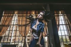 Mooie jonge vrouw in jeans en tennisschoenen voor grote Wi royalty-vrije stock afbeeldingen