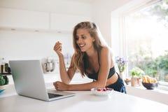 Mooie jonge vrouw in keuken met laptop stock afbeelding